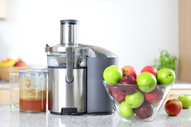 Apple juice on juicer machine - juicing concept. Apples in bowl