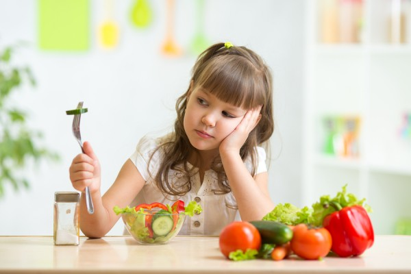 Child girl looks with disgust for healthy food