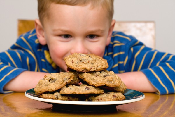 Willpower concept with boy staring down pile of cookies