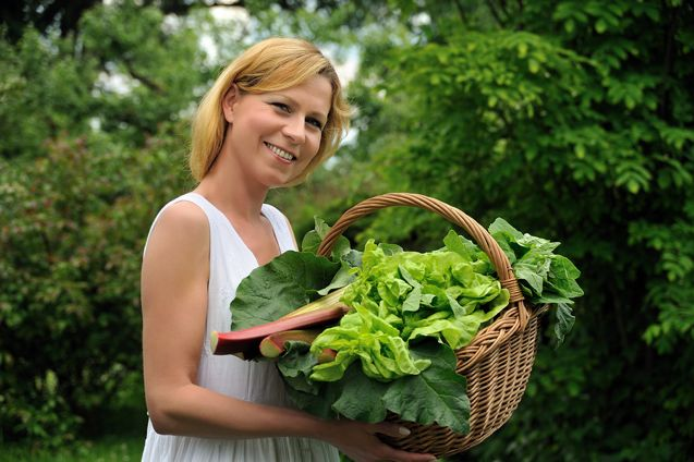 An image of young woman holding basket with vegetable