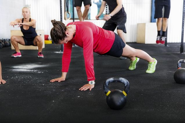 A fitness group training push ups, hang ups and squat at a gym center.