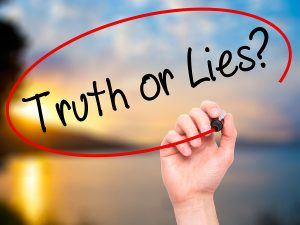Man Hand writing Truth or Lies? with black marker on visual screen. Isolated on nature. Business technology internet concept. Stock Photo